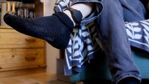 En person vars ansikte inte syns har lyft upp foten för att visa en elektronisk fotboja hen har runt fotleden