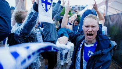 Väldigt glada fans. En man står och viftar en Finland-halsduk och ser ut att skrika något i förgrunden.