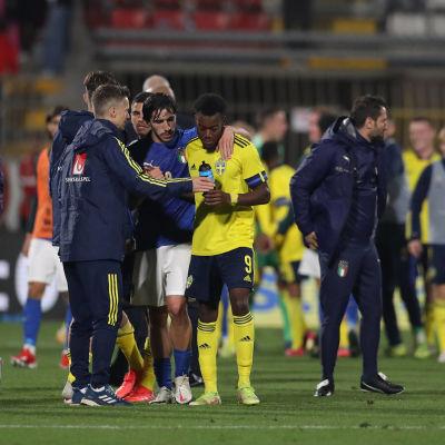 En hög med svenska och italienska ledare och spelare diskuterar efter en match.