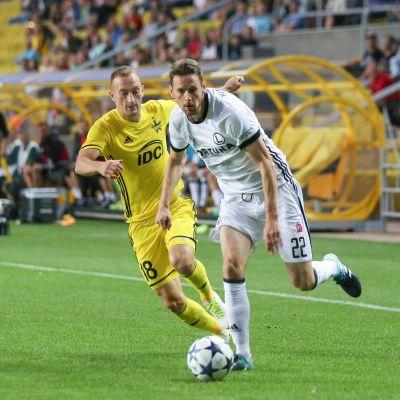 Kasper Hämäläinen löper med bollen mot FC Sheriff med en försvarare i ryggen.