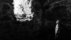 Pojke tittar ut genom glugg i Raseborgs slottsruins mur.