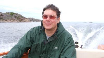 Asko Järvinen iklädd ljusbruna solglasögon kör motorbåt i skärgården.