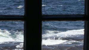 Näkymä Märketin majakan yläkerran huoneesta ikkunaristikon läpi, aallot lyövät rantaan