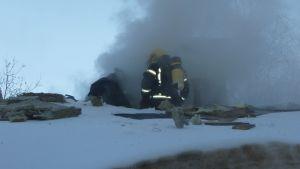Rökdykare i Fiskars sitter på ett snöigt tak, där massor av gråsvart rök bolmar ut.