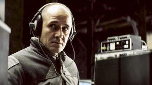 Stasin agentti Gerd Wiesler (Ulrich Mühe) kuulokkeet päässään.