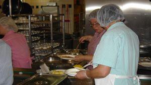 Kökspersonal gör matportioner i storkök