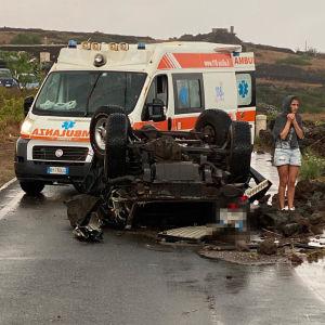 Åtminstone tio bilar slungades upp i luften av virvelvinden. Här har ambulansen kommit fram till en av bilarna.