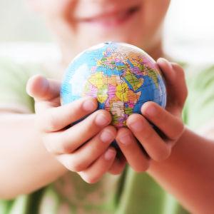 Ett barn håller en jordglob i sina händer