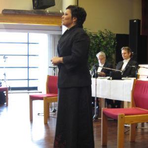 Sari Kaasinen pitkässä mustassa mekossa seisomassa pöydän edessä jonka takana istuu kaksi frakkipukuista miestä.