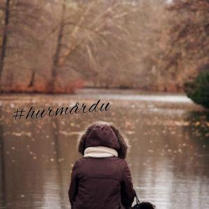 Ensam kvinna sitter på brygga och tittar ut över en sjö.