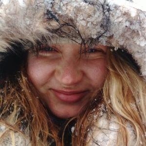 Lähikuva vaaleahiuksisesta hymyilevästä naisesta. Naisella on karvareunusteinen huppu päässä, joka on lumen kuorruttama. myös hiuksissa on lunta.