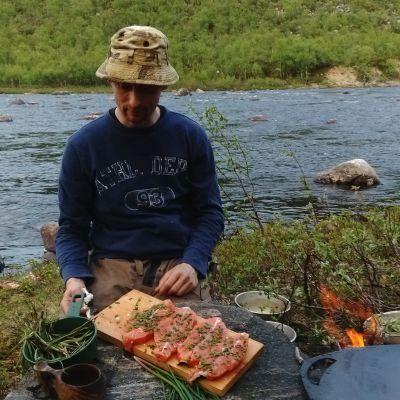Mies kokkaa joen äärellä. Laakean kiven päällä on puisella alustalla neljä lohimedaljonkia, kuksa ja yrttejä. Sivussa nuotiolla on muurinpohjapannu. Taustalla virtaa joki.