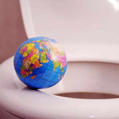 Jordglob som balanserar på en toalettstol.