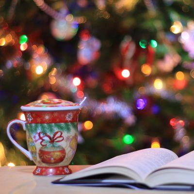 kuvassa kirja pöydällä avoinna, vieressä teemuki ja taustalla joulukuusi