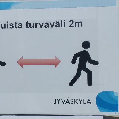 Kahden metrin turvavälistä muistuttava kyltti Jyväskylän koronatestauspaikalla.