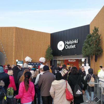 En massa människor vnätar utanför ett köpcentrum som snart ska öppnas.