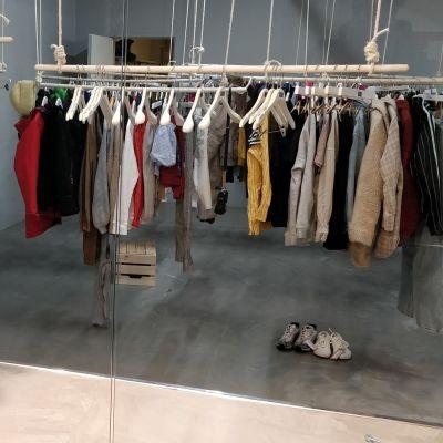 Vaatteita roikkuu rekeissä käytettyihin vaatteisiin erikoistuneessa myymälässä.
