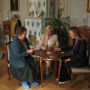 Tre damer spelar kort på Svartå slott