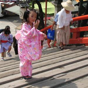 Kimonopukuinen japanilaistyttö menossa temppeliin.