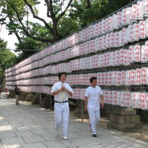 Kaksi valkopukuista miestä kävelee temppelin edustalla, takana kirjoitusmerkkikääröjä.
