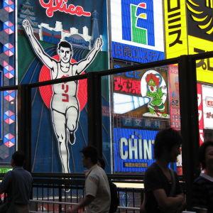 Neonvalomainoksia ja jalankulkijoita yöllä Osakassa.