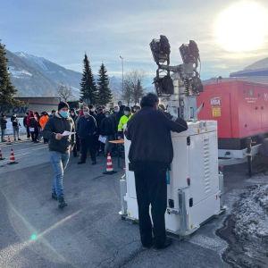 Bild på människor som står samlade på parkeringsplats. I bakgrunden skymtar österrikiska alper.