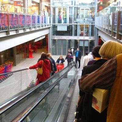 Kunder i en rulltrappa i ett köpcentrum.