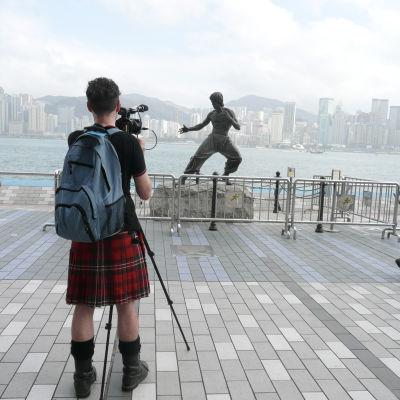 Kuvassa on sarjan tekijä Mark Cousins Hongkongissa Bruce Leen patsaalla. Yle kuvapalvelu.