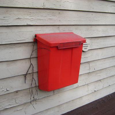 Röd postlåda på husvägg.