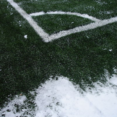 Vit gränslinje på grönt konstgräs samt snö.
