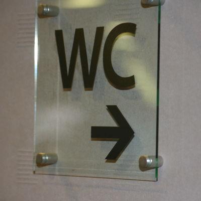 Skylt på väggen. På skylten står WC.
