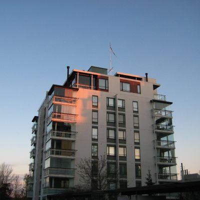 kvällssolens strålar träffar de högsta våningarna på ett vitt höghus.