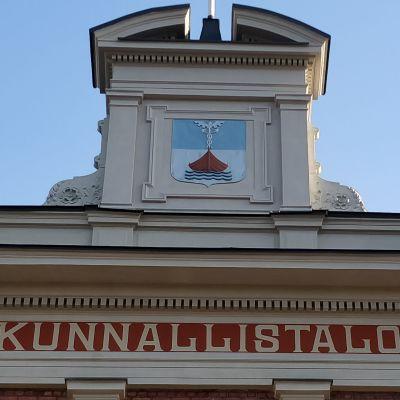 Yksityiskohta Jyväskylän kaupungintalon ulkoseinän yläreunasta, jossa lukee teksti Kunnallistalo. Katolla on myös uloke, jossa on Jyväskylän kaupungin vaakuna.