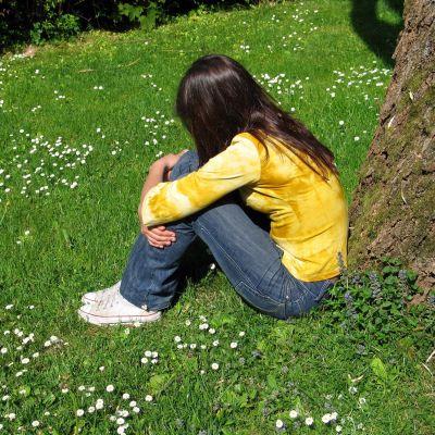 Ung kvinna sittande på gräsmatta.