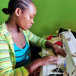 Nainen ompelee ompelukoneella