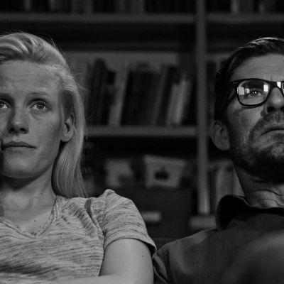 Närbild på Pihla (Laura Birn) och Eero (Tommi Korpela) som sitter bredvid varandra i soffan och ser på tv.