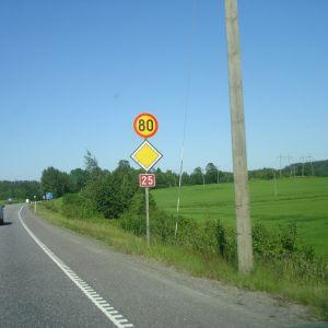 En bil kör på väg där skylten visar hastighetsbegränsning på 80 kilometer per timme.