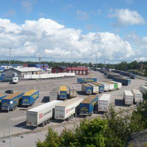 Stuveribolaget Hangö Stevedorings byggnader och tiotals containers på hamnplanen i Västra hamnen i Hangö en solig sommardag.