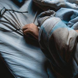 Kvinna som ligger i sängen.