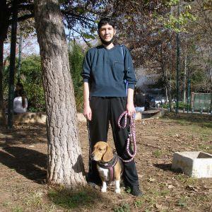 Nuori nainen seioo koiran kanssa puistossa
