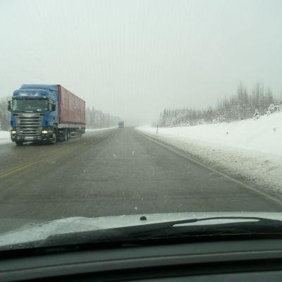 Långtradare kör på snöig väg