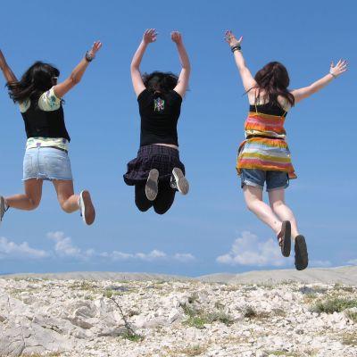 tre flickor hoppar upp i luften