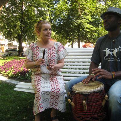 Francis Oyeyiola soittaa ghanalaista rumpua ja tapahtuman koordinaattori Carina Engström kapuloita.