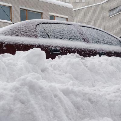 Tienvarteen pysäköity henkilöauto hautautuneena lumihankeen.