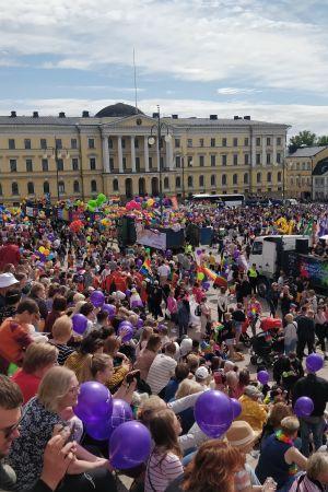 Prideparad i Helsingfors. Människor sitter på Domkyrkans trappor och väntar.