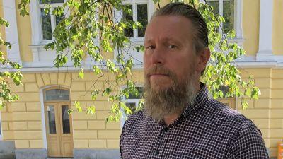 En man med grått hår och långt grått skägg står ute. I bakgrunden en stor gul byggnad, gamla stadshuset i Ekenäs. Sommar.