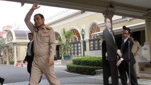 Prayuth Chan-ocha vinkar adjö efter att han placerat en kartongdocka framför journalisterna.
