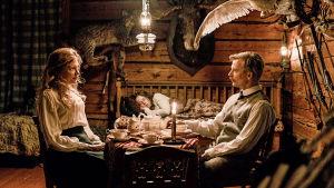 Aktivistit-sarjan kaksi näyttelijää istuvat pöydän ääressä ja katsovat toisiaan silmiin.