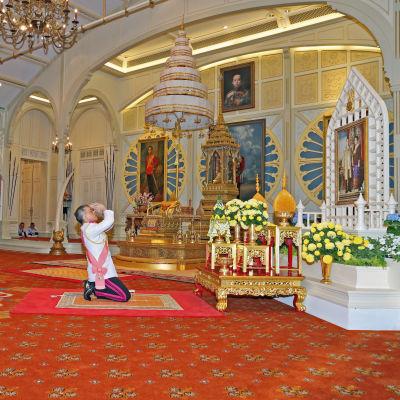 Thailands nye kung Vajiralongkorn knäböjer inför ett porträtt av sin far, kung Bhumibol