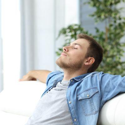 Mies lepää sohvalla istuen kädet levällään.